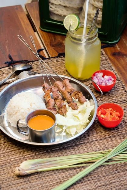 Satay de comida indonésia servido com molho de amendoim e rolo de bolo de arroz Foto Premium