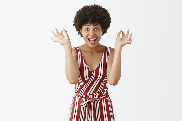 Satisfeita e animada, atraente mulher de pele escura, de macacão listrado vermelho, mostrando gestos de ok ou ok perto do rosto e sorrindo alegremente Foto gratuita