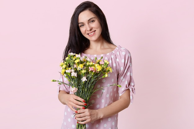 Satisfeito jovem europeia bonita com sorriso gentil, usa vestido de bolinhas, detém o buquê de flores, feliz em receber do marido, modelos em rosa pastel. Foto gratuita