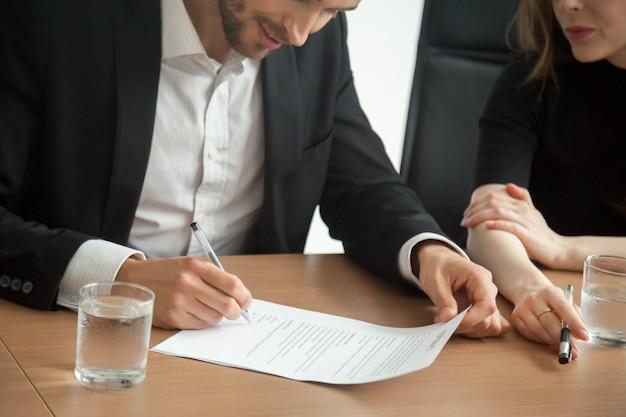 Satisfeito, sorrindo, homem negócios, em, paleto, assinando, contrato, em, reunião, conceito Foto gratuita