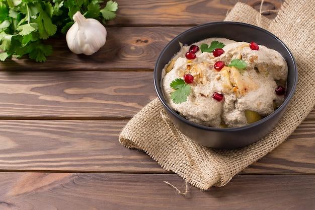 Satsivi georgiano tradicional com frango, nozes e romã Foto Premium
