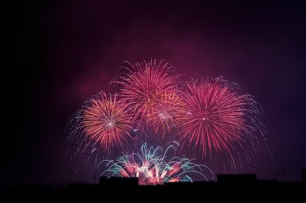 Saudação bonita colorida dos fogos-de-artifício contra o céu nocturno escuro. Foto Premium