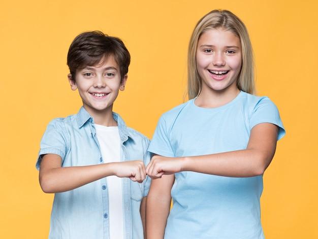 Saudação de punho de irmãos jovens Foto gratuita