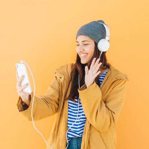 Saudação feliz senhora durante uma chamada de vídeo com um telefone inteligente Foto gratuita