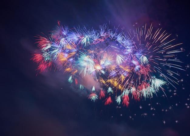 Saudação linda colorida de fogos de artifício contra o céu noturno escuro Foto Premium