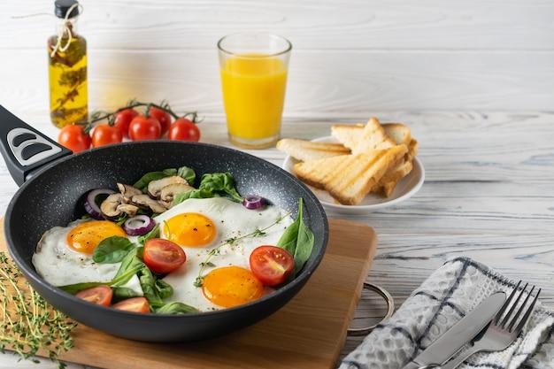 Saudável café da manhã com ovos fritos, tomate, cogumelos e folhas de espinafre Foto Premium