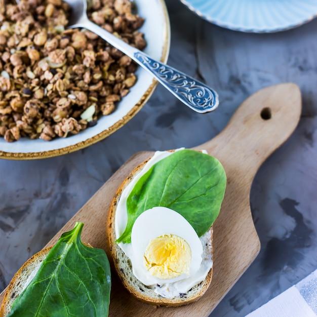 Saudável café da manhã saudável - muesli, sanduíche com ovo, café, laranja e suco Foto Premium
