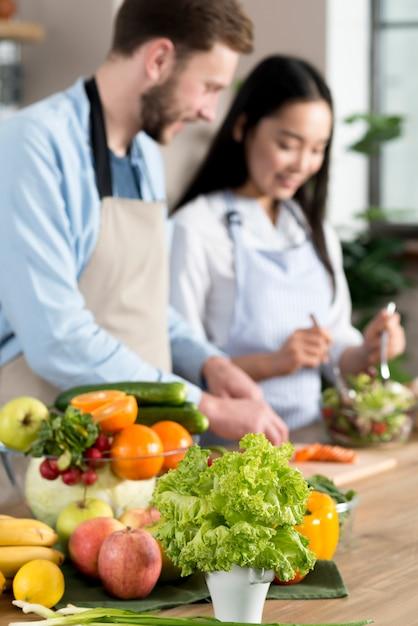 Saudável, frutas legumes, frente, defocussed, par, preparando alimento, em, cozinha Foto gratuita