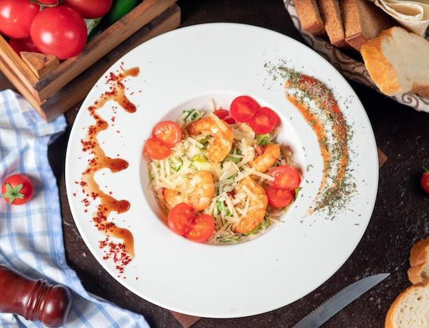 Saudável grelhado crevettes caesar salad com queijo, tomate cereja e alface Foto gratuita