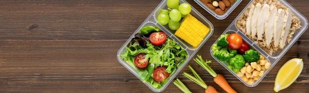 Saudável pronto para comer comida em caixas de refeição no fundo da bandeira de madeira Foto Premium