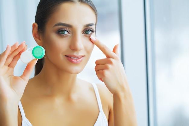Saúde. a rapariga prende a lente de contato nas mãos. retrato de uma mulher bonita com olhos verdes e lentes de contato. Foto Premium