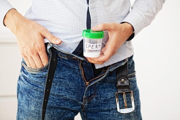 Saúde. amostra de esperma. doador esperma perto conceito de esperma do banco. infertilidade, um homem segurando no recipiente de mãos com esperma Foto Premium