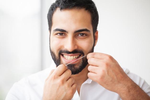 Saúde dental. homem, com, bonito, sorrizo, fio dental, dentes saudáveis Foto Premium