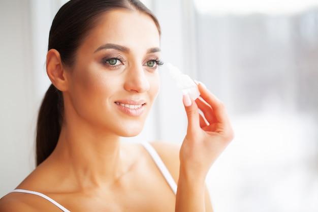 Saúde e beleza. cuidado do olho jovem mulher bonita que guarda gotas para os olhos. Foto Premium