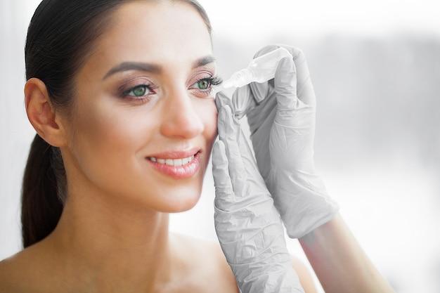 Saúde e beleza. cuidados com os olhos. mulher jovem e bonita segurando gotas para os olhos. boa visão. garota feliz com olhar fresco Foto Premium