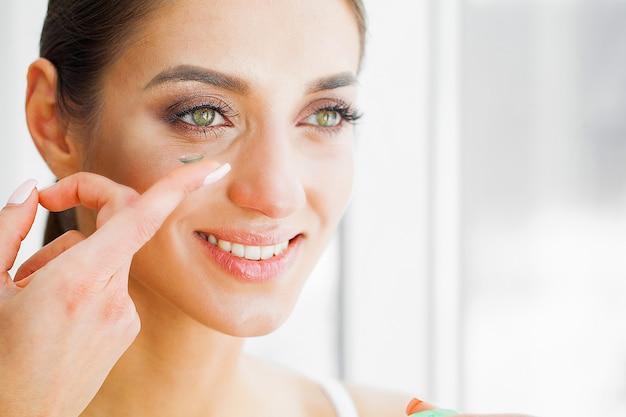 Saúde e beleza. linda garota de olhos verdes detém lente de contato no dedo. cuidados com os olhos. Foto Premium