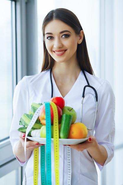 Saúde e beleza. médico sério escreve plano dieta. mulher senta-se no escritório. doutor novo com sorriso bonito e fruta fresca. Foto Premium