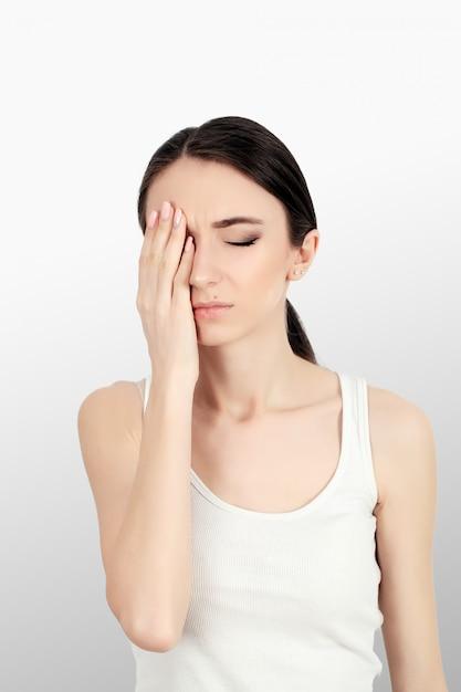 Saúde. mulher com dor, sentindo-se mal e doente, tendo dor de cabeça e febre, segurando a mão. linda garota cansada infeliz, sofrendo de dor de cabeça dolorosa e estresse. cuidados de saúde. Foto Premium