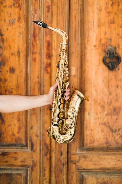 Saxofone dourado com fundo de madeira Foto gratuita