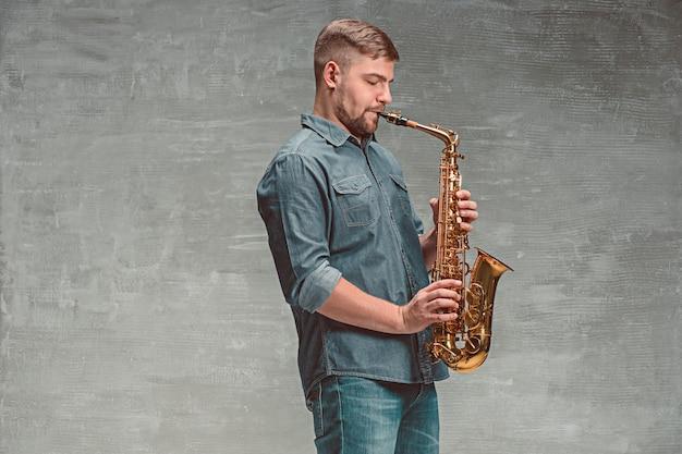 Saxofonista feliz tocando música no saxofone sobre cinza Foto gratuita