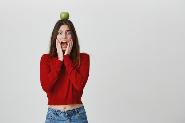 Scareming garota preocupada segurando a maçã na cabeça como um alvo de arqueiro Foto gratuita