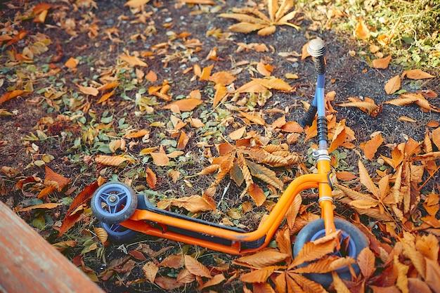 Scooter infantil encontra-se em um parque infantil em folhas amarelas Foto Premium