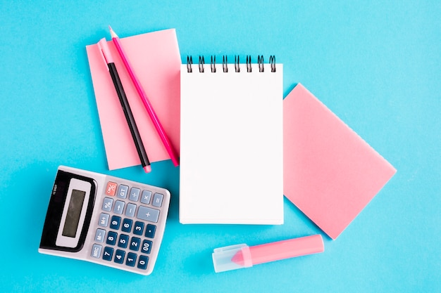 Scratchpad e ferramentas de escritório na superfície azul Foto gratuita