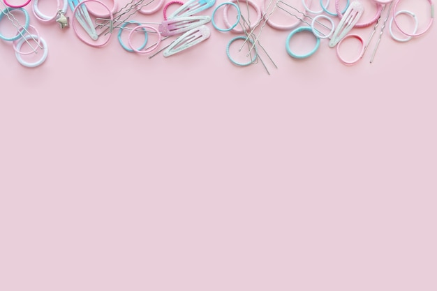 Scrunchies de cabelo e grampos de cabelo no fundo rosa, conceito de beleza, lay plana Foto Premium