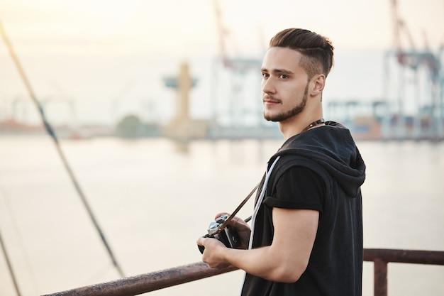 Sea atrai este fotógrafo. retrato ao ar livre de cara jovem e atraente em pé no porto, desfrutando de olhar para o mar enquanto segura a câmera, procurando uma boa localização para tirar foto, olhando de lado Foto gratuita