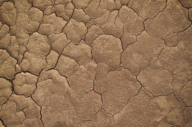 Seca terra rachada durante em uma estação chuvosa, porque a falta de escassez de chuva de água rachada textura de fundo do solo Foto Premium