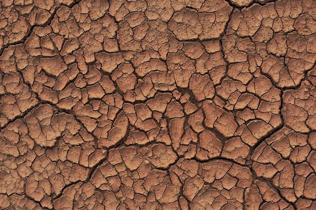 Seca terra rachada durante em uma estação chuvosa, porque a falta de escassez de chuva de água rachada textura do solo Foto Premium