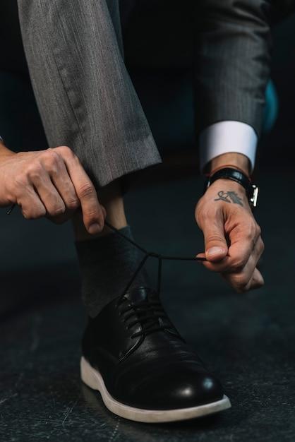 Seção baixa da mão do empresário amarrando o cadarço Foto gratuita