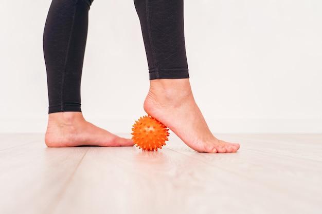 Seção baixa da menina que exercita com a bola do esforço no hospital. bola de massagem sob os pés. Foto Premium