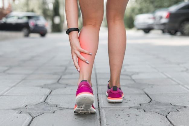 Seção baixa, de, femininas, atleta, ficar, rua, tendo, dor, em, perna Foto gratuita
