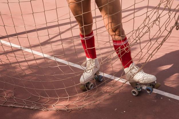Seção baixa, de, mulher, desgastar, branca, patim rolo, ficar, perto, a, futebol, meta, rede Foto gratuita