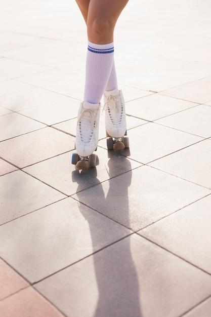Seção baixa, de, mulher, em, patim rolo, ficar, com, cruzado, pernas, ligado, chão Foto gratuita