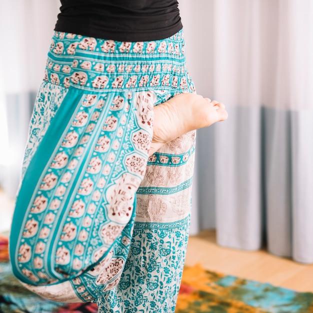 Seção baixa de mulher fazendo yoga prática em casa Foto gratuita