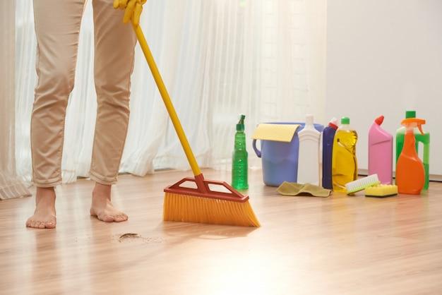 Seção baixa de mulher irreconhecível, varrendo o chão com vassoura Foto gratuita