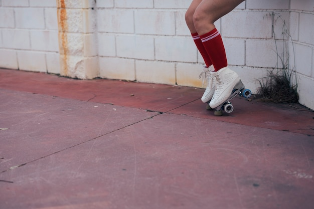 Seção baixa, de, patinador feminino, equilibrar, ligado, patim rolo Foto gratuita