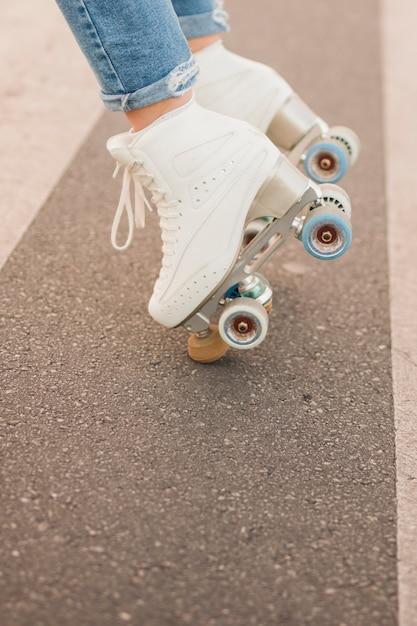 Seção baixa, de, pé mulher, desgastar, branca, patim rolo, equilibrar, ligado, estrada Foto gratuita