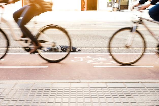 Seção baixa de pessoas andando de bicicleta na ciclovia Foto gratuita