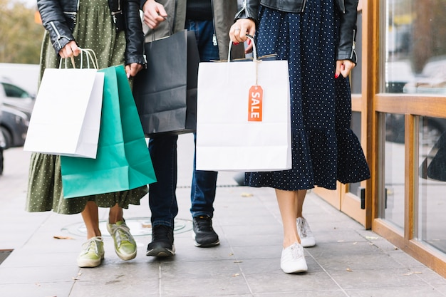Seção baixa, de, um, amigos, andar, ligado, calçada, com, coloridos, bolsas para compras Foto gratuita
