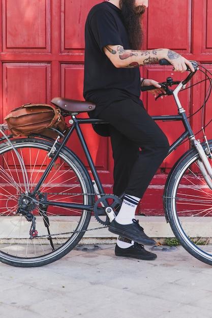 Seção baixa, de, um, assento homem, com, bicicleta, frente, porta Foto gratuita