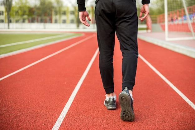 Seção baixa de um atleta do sexo masculino andando na pista de corrida vermelha Foto gratuita
