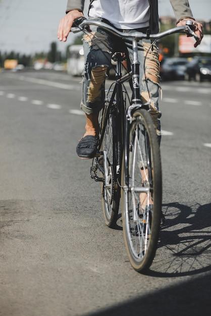 e91d0d0179 Seção baixa do homem andando de bicicleta na estrada