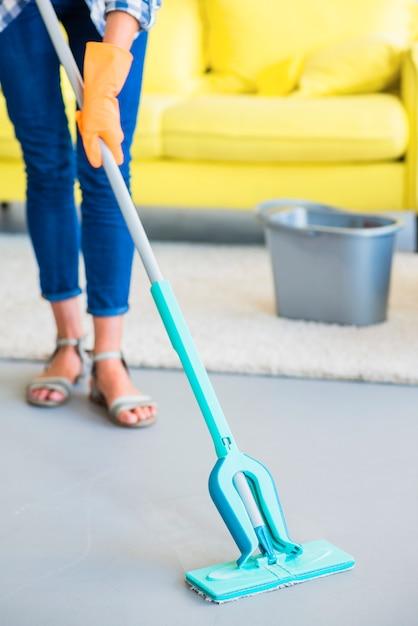Seção baixa do zelador feminino, limpando o chão com esfregão Foto gratuita