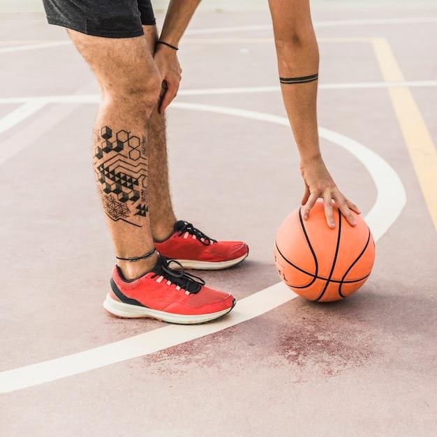 Seção baixa, vista, de, um, homem, apanhar basquetebol, em, corte Foto gratuita