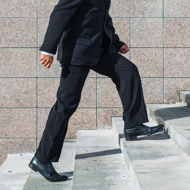 Seção baixa, vista, de, um, homem negócios, escalando escadaria Foto gratuita