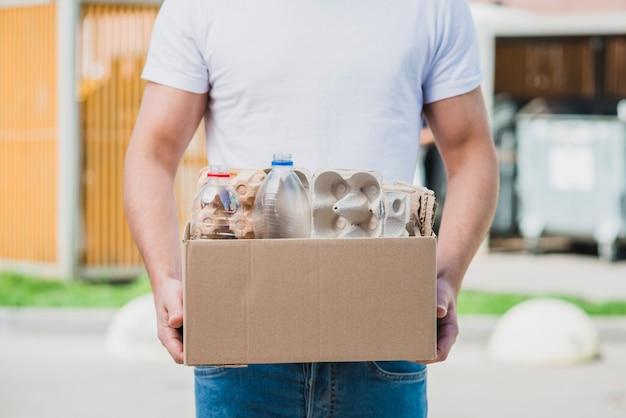 Seção intermediária da caixa de papelão reciclável com item reciclável Foto gratuita