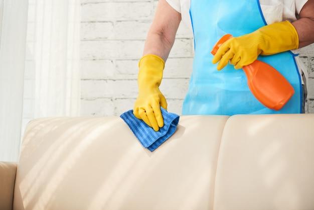 Seção intermediária da empregada irreconhecível, limpando o sofá de couro com spray de polimento de couro Foto gratuita